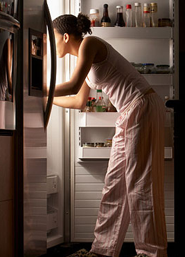 Simple-steps-to-slash-calories-woman-looking-into-fridge-full